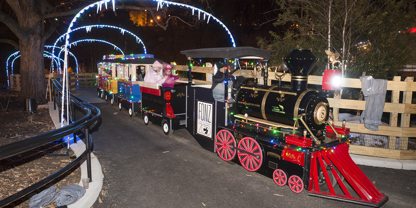 Guests dressed in winter clothing ride a miniature train alongside a picket fence under decorative lit archways at the Zoo