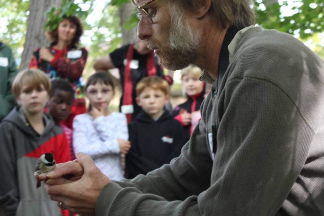 SMBC researcher Bob Reitsma holds a small bird and talks to a group of students and teachers about the Neighborhood Nestwatch program