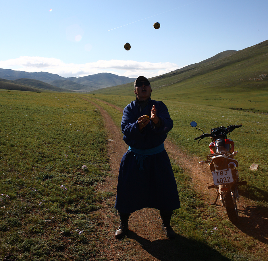 A park ranger in Hustai National Park, Mongolia, juggling next to a motorbike