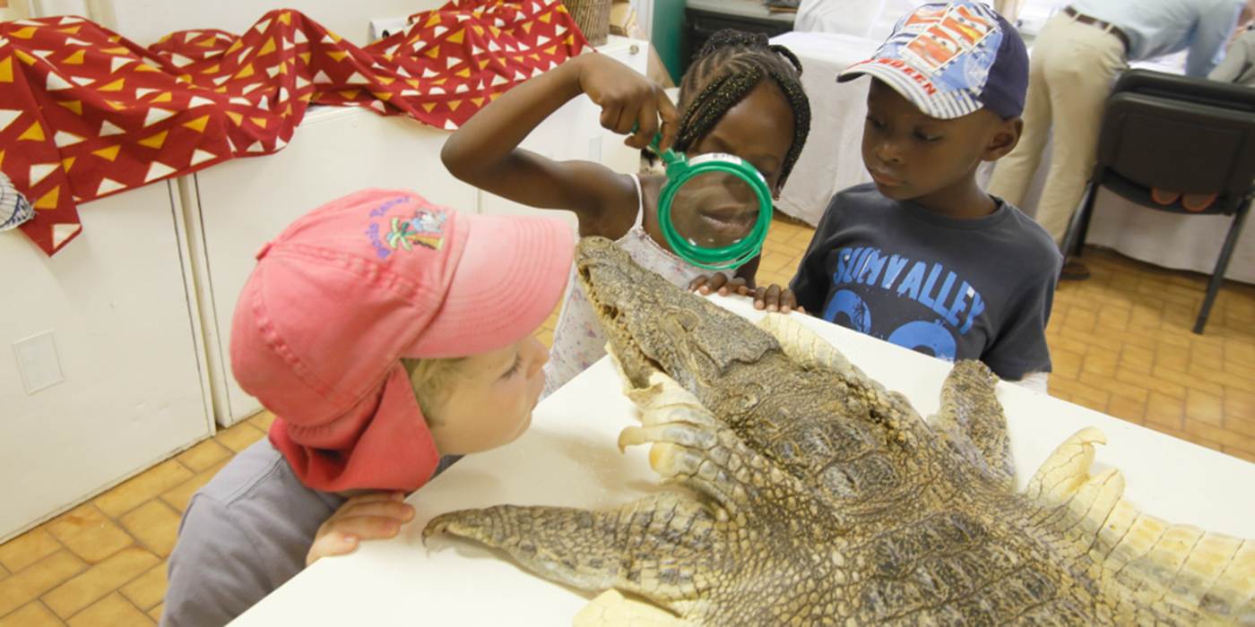 three children examining an alligator skin with a magnifying glass