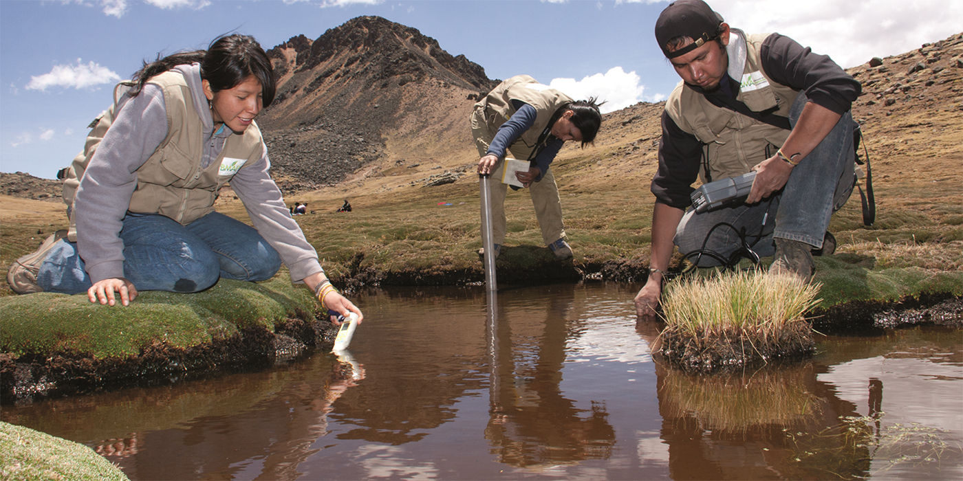 three researchers collecting water samples