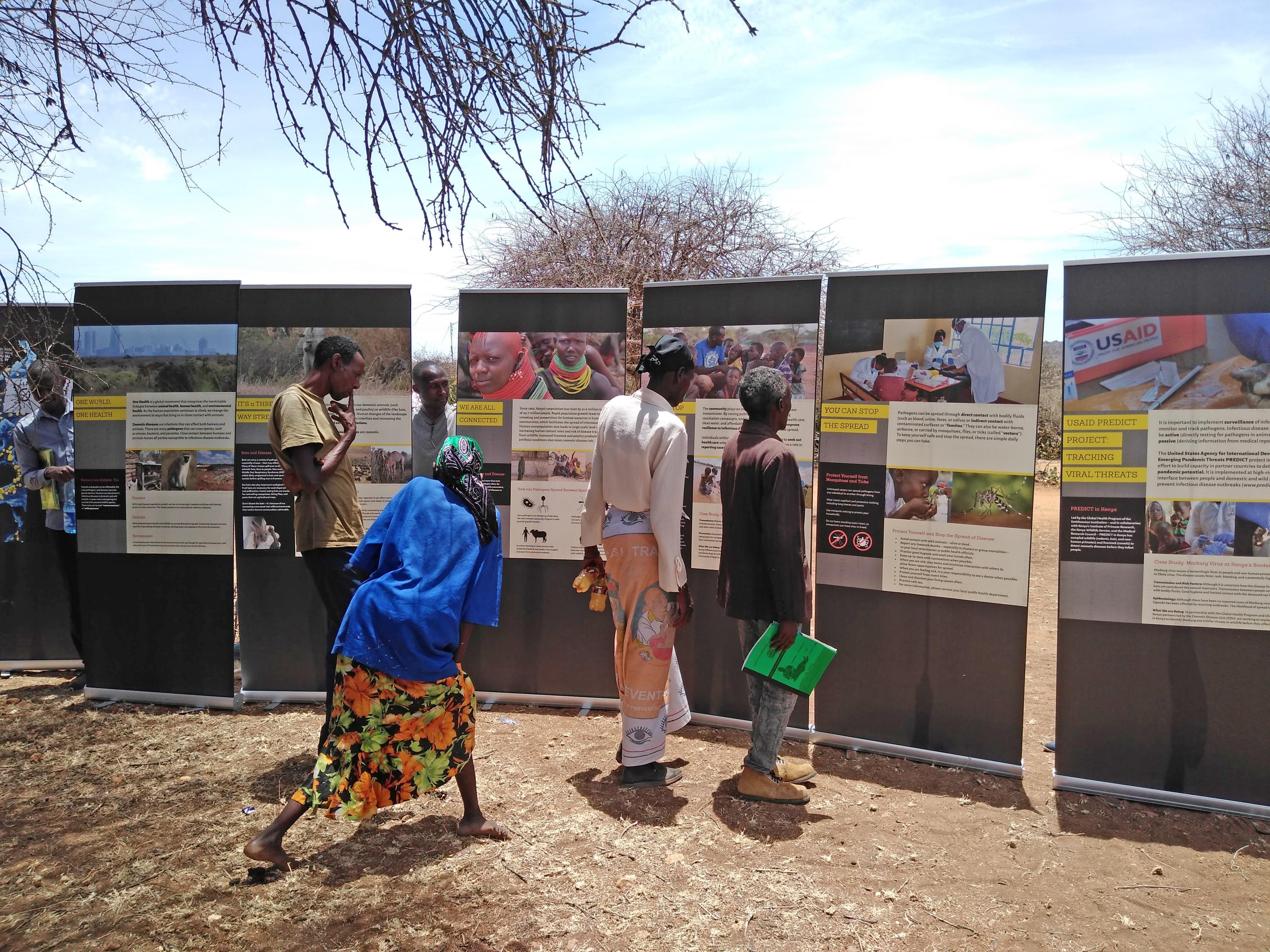 Community members in Laikipia, Kenya, examine exhibit panels from the mobile Outbreak DIY exhibit