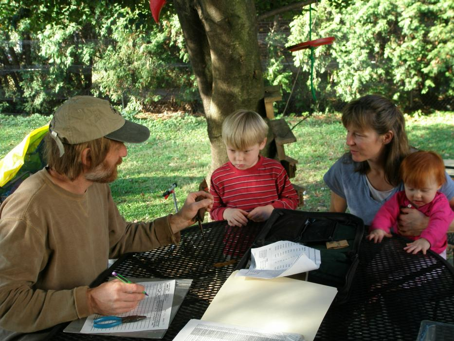 A researcher with the Smithsonian Migratory Bird Center talks to a mother and two young children about birds. They are seated around a table in their backyard with a tree and grass in the background.