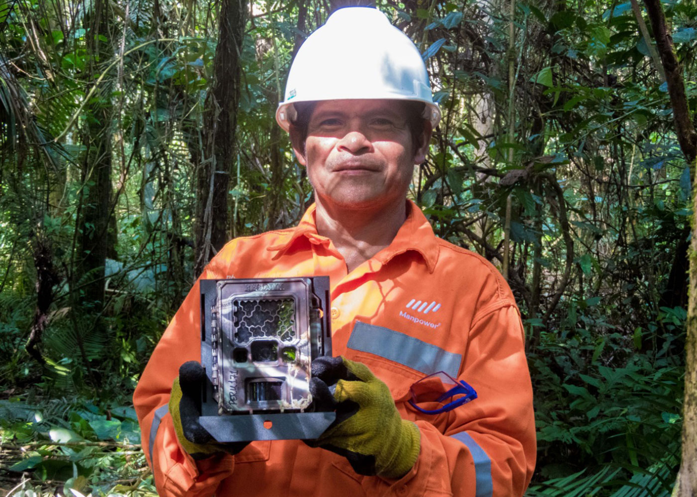 A man, named Angel Mashingash Petsa, dressed in an orange work suit and construction hat holds a camera trap device