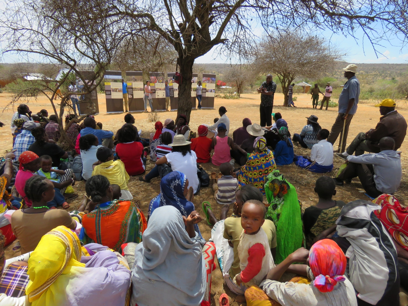 Community members in Laikipia County, Kenya, sit outside as someone gives a presentation on exhibit panels from the mobile Outbreak DIY exhibit.