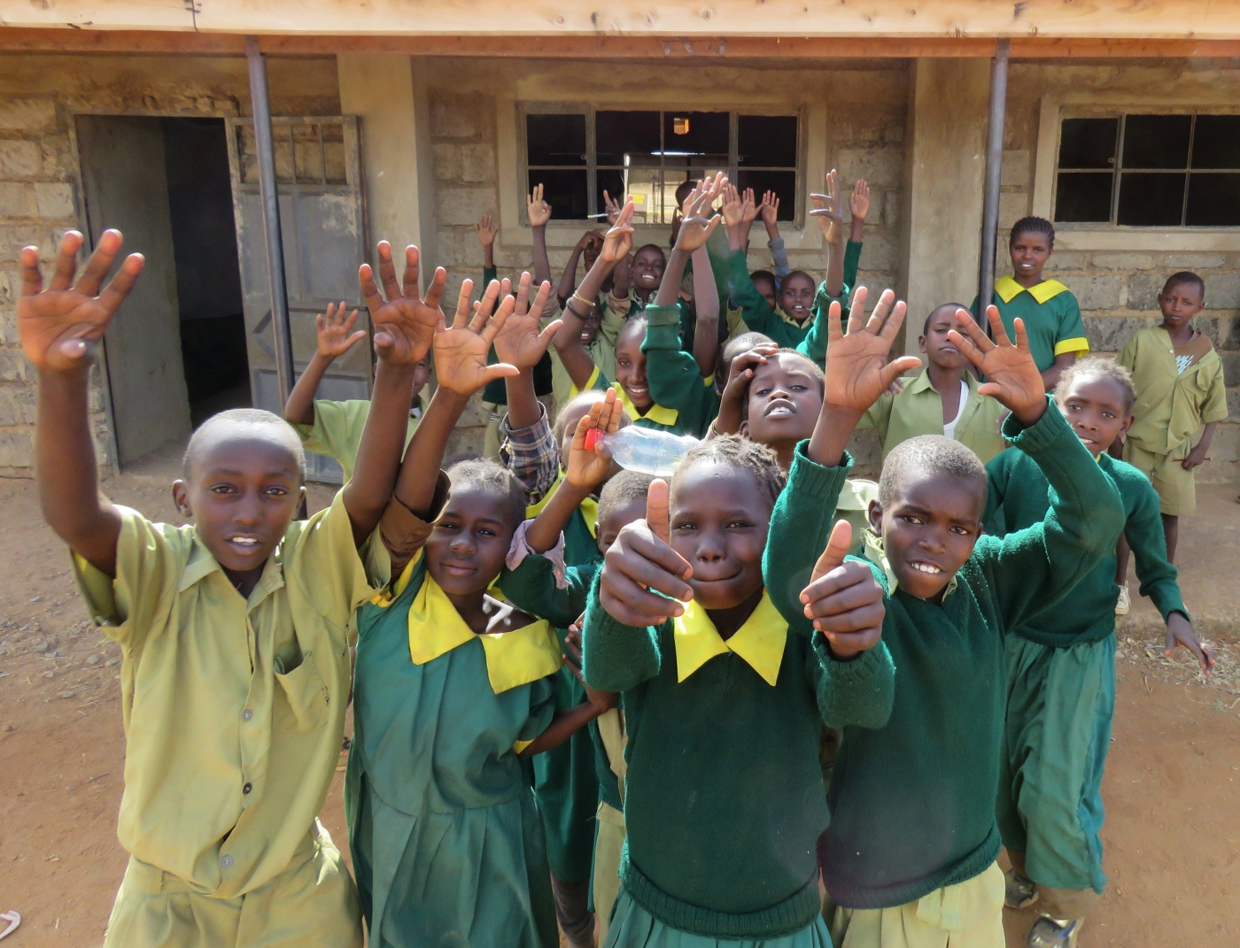 Primary school students in Laikipia, Kenya, pose for a photo in front of a building. Some of the students are raising their hands and giving a thumbs up