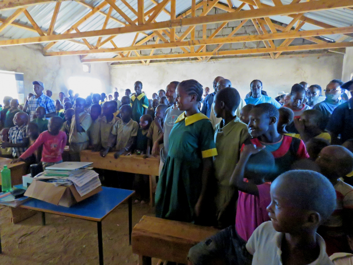 A group of primary school students in a classroom in Laikipia, Kenya, watch a documentary. Some are seated and some are standing.
