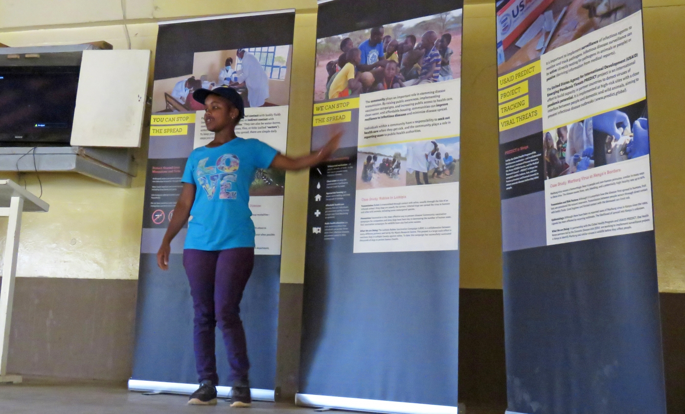 Public health graduate student Caroline Cherotich Mutai gives a presentation on the mobile Outbreak DIY exhibit. She is standing in front of the mobile exhibit panels and points to one as she speaks.