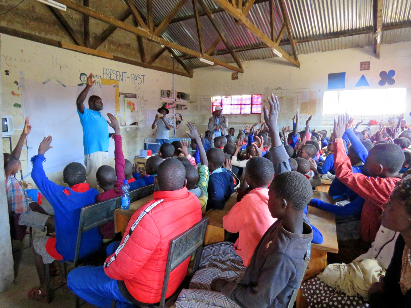 A classroom of students in Laikipia County, Kenya, raises their hands to ask questions