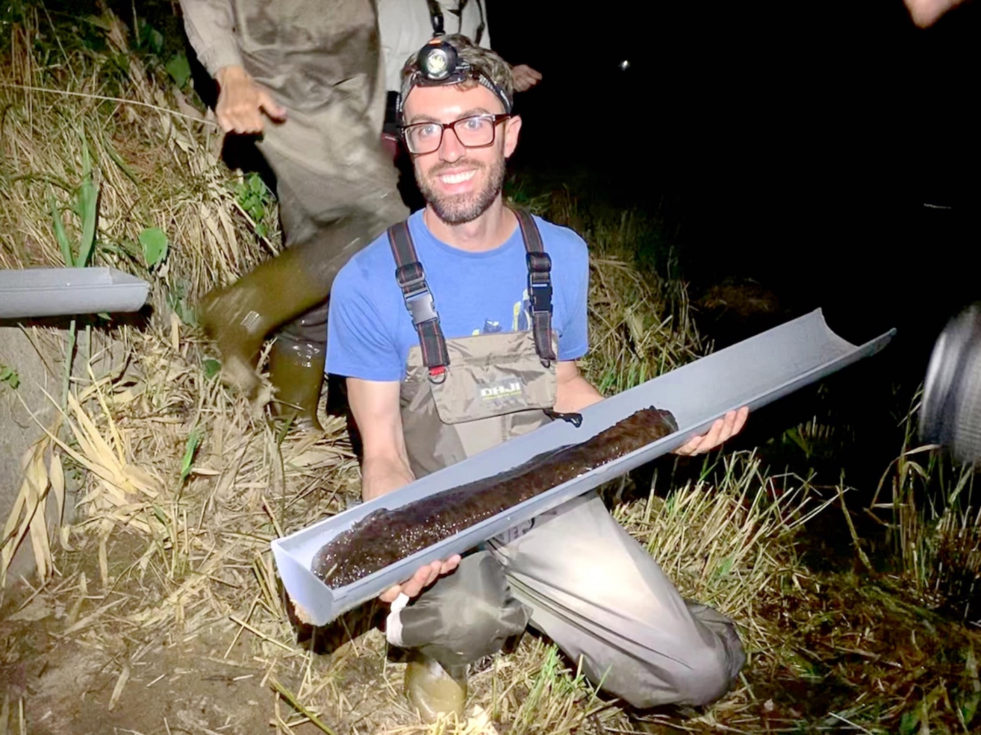 Reptile Discovery Center keeper Matt Neff with a wild Japanese giant salamander in Hiroshima, Japan.