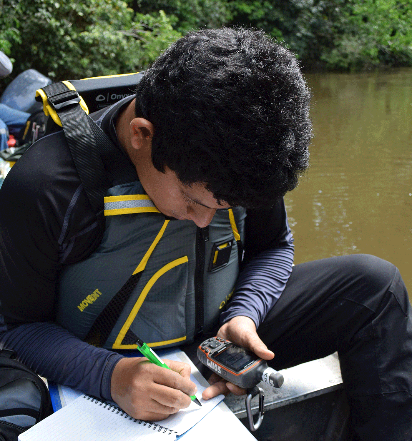 A fish researcher (ichthyologist) records GPS data from a small boat in a river in Peru