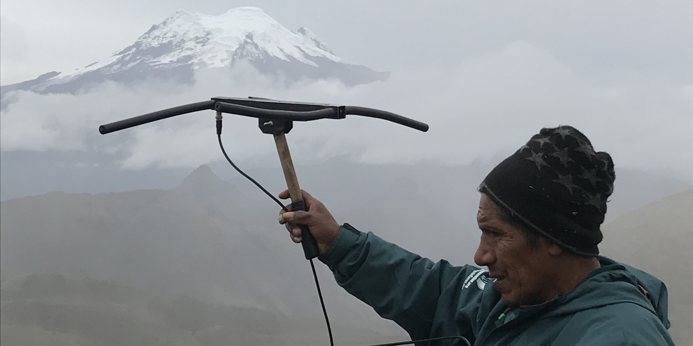 A researcher in Ecuador holds a transceiver up toward a tall, snowcapped mountain obscured by fog and clouds