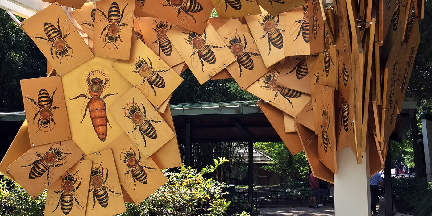 A series of hand-painted bees on gold-painted wooden boards attached to a structure. The bees are an installation called Colony Expanse by artist Matthew Willey as part of his The Good of the Hive initiative