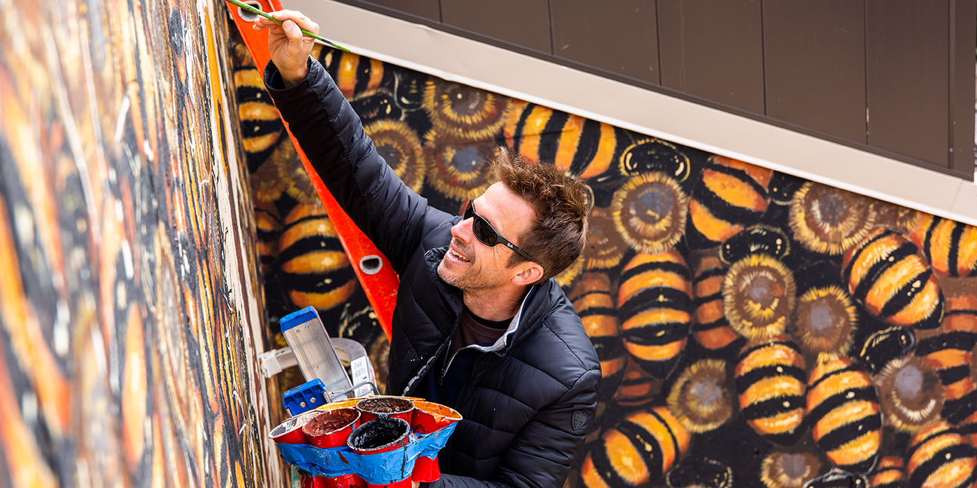 Artist Matthew Willey paints a bee mural on the Smithsonian's National Zoo's Great Ape House