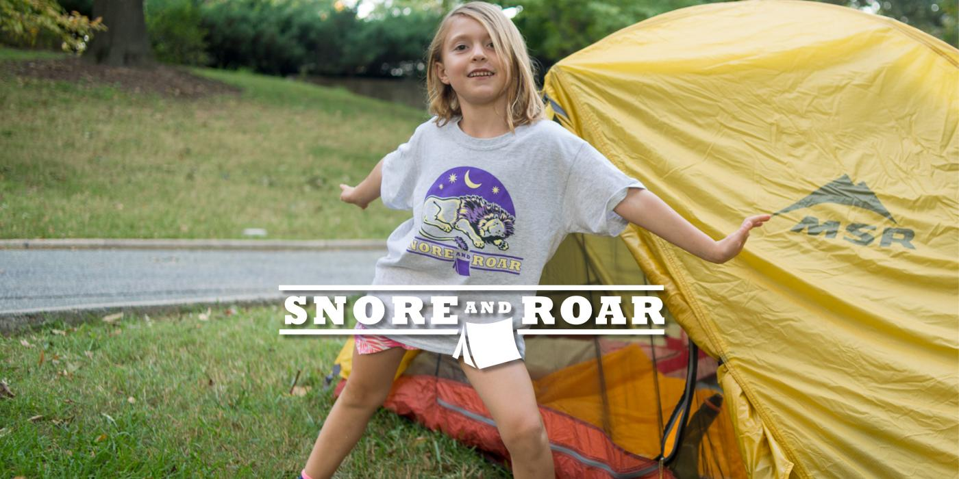 """A child poses in front of a yellow tent at a Zoo sleepover with the text """"Snore and Roar"""""""