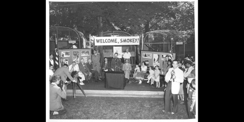 "a group of people stand around a podium with a banner behind it that says ""Welcome, Smokey"""