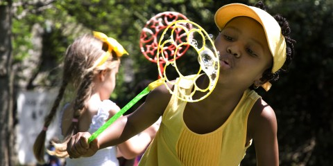 child blowing bubles during easter monday event
