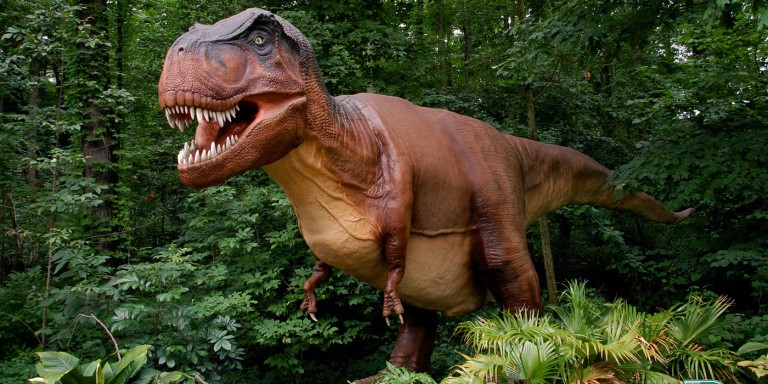 A large animatronic T-rex dinosaur standing in a forested area