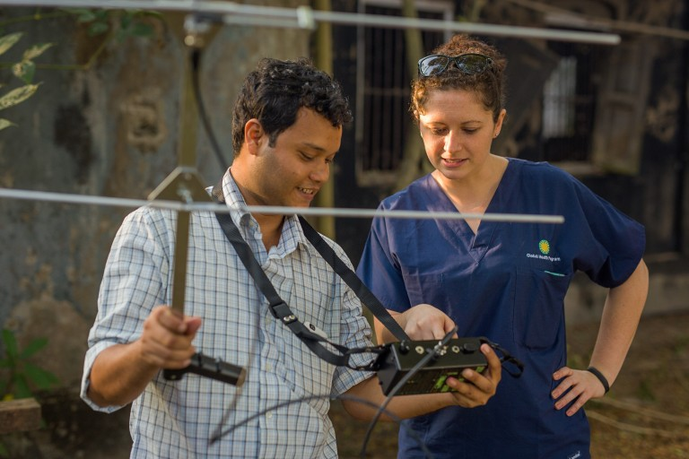 Global Health Program researcher Jen Kishbaugh works with field researcher Kyaw Yan Naing Tun in Myanmar to use a transceiver