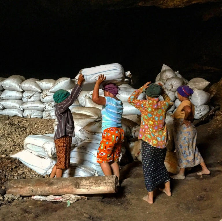 A family in Myanmar walks barefoot through a bat cave gathering bat guano in bags to sell