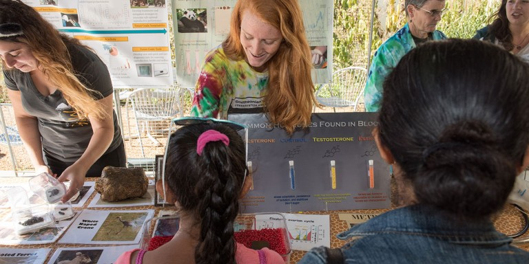 A researcher at the Smithsonian Conservation Biology Institute points to a scientific poster and talks to students about her work