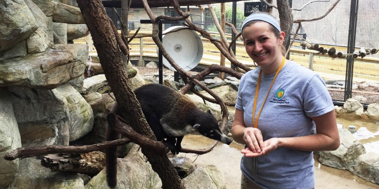 Animal keeper Kara Ingraham with a white-nosed coati at the Small Mammal House.