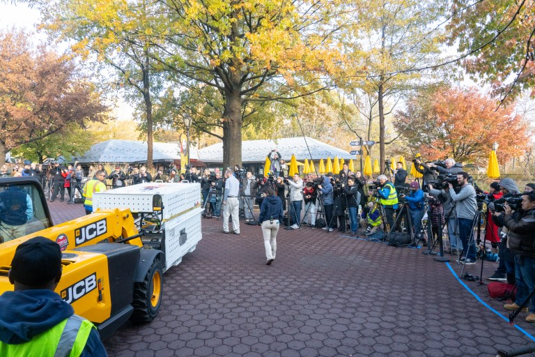 A yellow fork lift carries a crate holding giant panda Bei Bei past a line of videographers and photographers