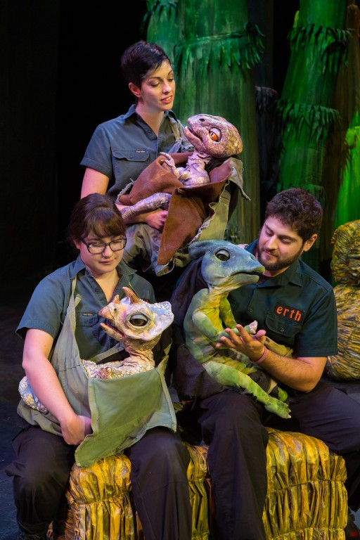 """Three """"Erth's Dinos Zoo Live"""" cast members hold small, winged dinosaur puppets on stage"""