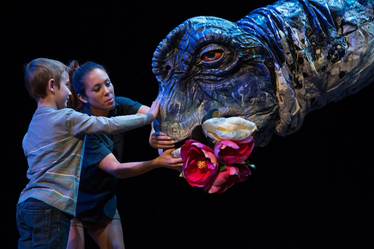 """During an """"Erth's dinos zoo live"""" performance, a cast member and child put flowers in the mouth of a larger-than-life dinosaur puppet"""