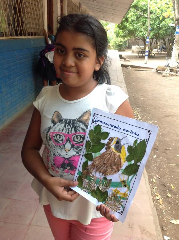 A student displays her artwork.