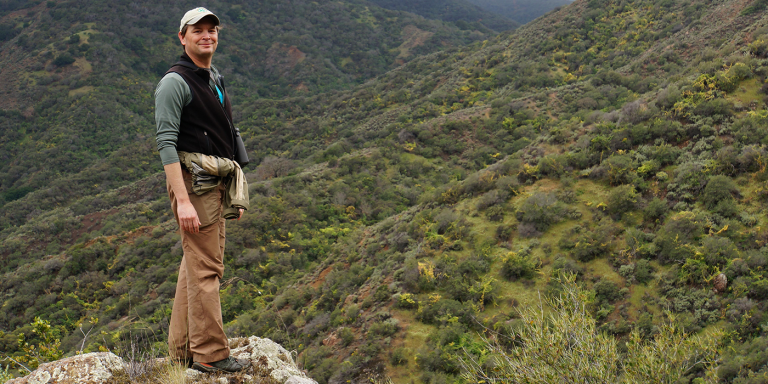 A man wearing a vest and khaki pants stands on a rock overlooking a green valley