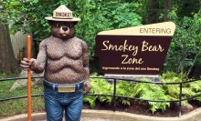 "A Smokey Bear statue beside a sign that says ""Entering Smokey Bear Zone"" at the Smithsonian's National Zoo"