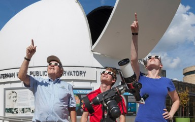 Three people outside of an observatory looking up and pointing at the sky. They are wearing eclipse-safe glasses.