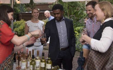 A vendor handing glasses of wine to a group of men and women