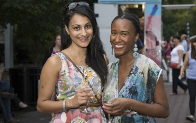 Two women holding glasses of wine and posing for a photo