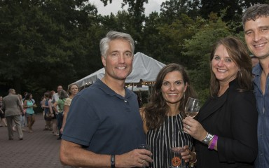 Two men and two women posing for a photo and holding glasses of wine