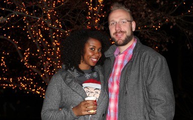Couple standing in front of tree with lights