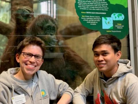 Curator of primates Meredith Bastian and international exchange student Dr. Jati in front of the Smithsonian's National Zoo's orangutan habitat