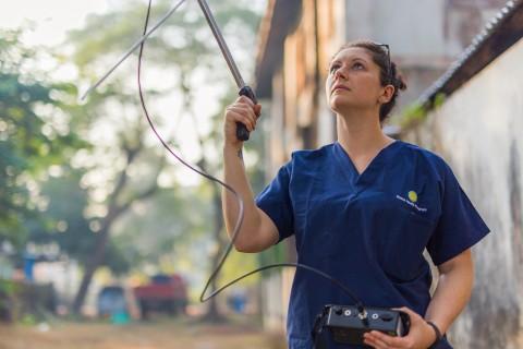 Global Health Program researcher Jen Kishbaugh uses a transceiver during a fruit bat study in Myanmar