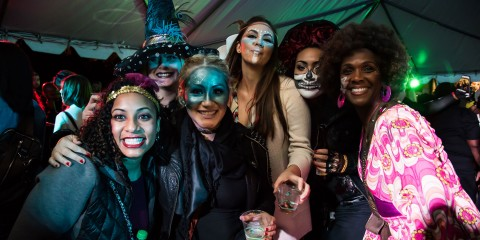 A group of six women dressed up in Halloween costumes and face paint pose for a photo at Night of the Living Zoo