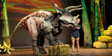 A woman stands on stage next to a large dinosaur puppet