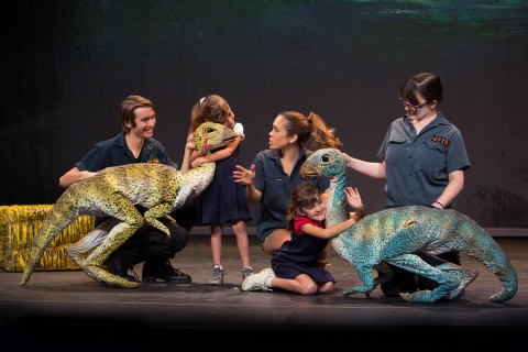"During a production of ""Erth's dinos zoo live"" cast members and two children interact with two dinosaur puppets"