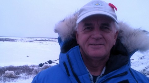 Animal behaviorist Donald Moore wearing a parka and hat in a snowy area where a polar bear can be seen in the background