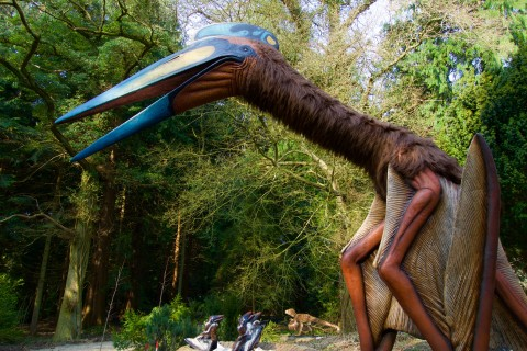 A large, animatronic Quetzalcoatlus dinosaur and smaller, baby animatronic Quetzalcoatlus dinosaurs on exhibit in a wooded area