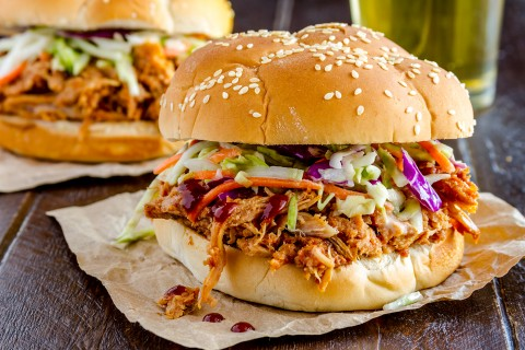 A pulled pork sandwich with cabbage slaw on a sesame seed bun sitting on a napkin