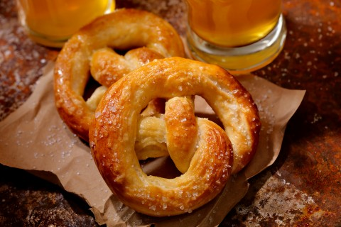Two soft pretzels sitting on top of a brown sheet of paper with two beers in the background
