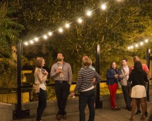A group of people talking and enjoying drinks under lights outside the Great Cats exhibit in the evening at the Smithsonian's National Zoo