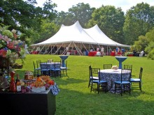An event tent, tables and chairs set up in a grassy green meadow surrounded by trees on a sunny day at the Smithsonian's National Zoo