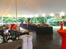 A bar and decorated tables set up under a large event tent lit up with lights in the Great Meadow