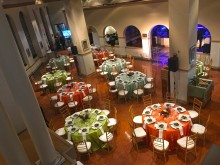 An aerial view of colorful round tables decorated for a private, catered event in the Amazonia science gallery at the Smithsonian's National Zoo